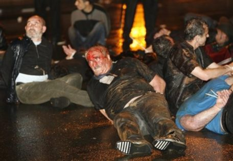 CORRECTS BYLINE - Arrested opposition activists, one with bloody head, lay on the ground at an anti-presidential rally  in front of the parliament building in Tbilisi, Georgia, early Thursday, May 26, 2011. On Thursday, May 26, 2011, Georgia marks its Independence Day. (AP Photo/Shakh Aivazov)